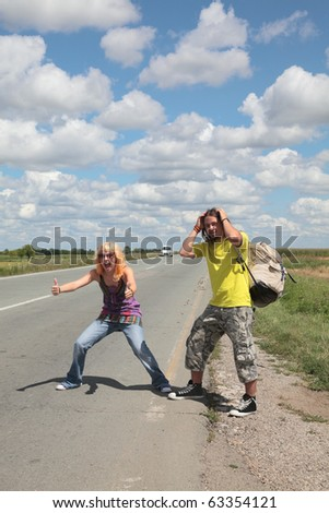 Caucasian smiling  girl and boy gesturing and hiking at a road