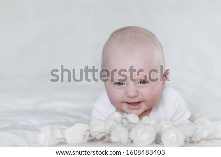 Caucasian smiling infant lying on stomach dressed in white on white background with white flowers in front of him.