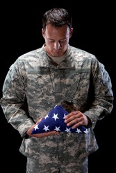 Caucasian soldier holds an American flag