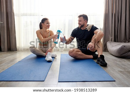 caucasian sportive couple after training workout at home, take a break sitting on fitness mat Photo stock ©
