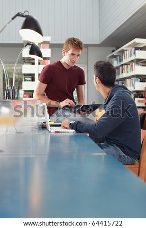 caucasian students with laptop computer talking in library. Vertical shape, copy space, focus on background