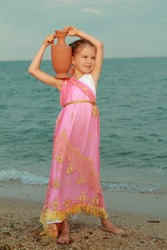 Caucasian sweet young girl in pink tunic in antique style is holding an antique amphora on the sea coast/Greek goddess of beauty