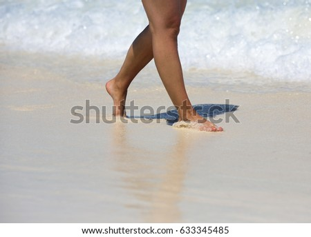 Caucasian tanned woman is walking on the beach. Sand and water splashing on the feet. White sand beach with small waves. Clear water and sunny day. Vacation concept image. #633345485