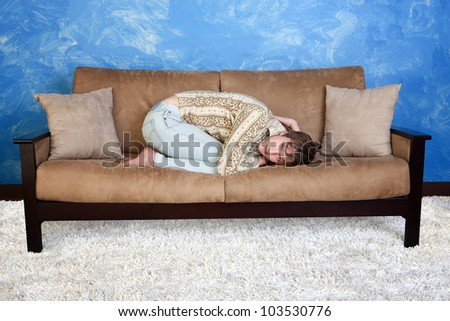 Caucasian teen in curled up position on sofa