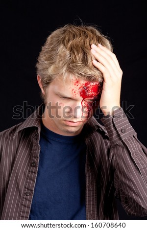 Caucasian teenage boy with blonde hair holding head after serious injury