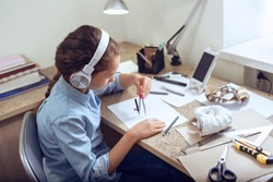 Caucasian teenage girl in headphones is learning distant form home using smartphone. Girl is drawing sitting at the table. Art, education, creativity, teenage hobbies