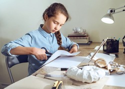 Caucasian teenage girl is learning distant form home using smartphone. Girl is cutting paper sitting at the table. Art, education, creativity, teenage hobbies