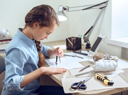 Caucasian teenage girl is learning distant form home using smartphone. Girl is drawing sitting at the table. Art, education, creativity, teenage hobbies