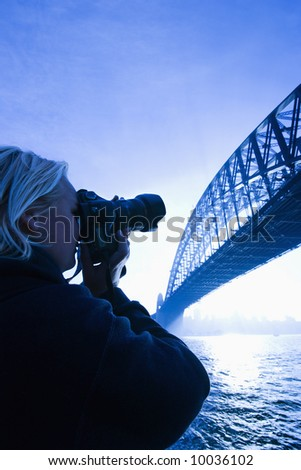 Caucasian teenage male photographing Sydney Harbour Bridge at dusk with view of Sydney Harbour, Australia.