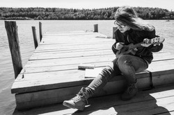 Caucasian teenager girl in glasses plays ukulele on a wooden pier, black and white outdoor photo