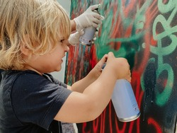 Caucasian three years old blonde child painting graffiti with a spray at the wall with effort face