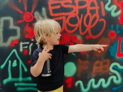 Caucasian three years old boy pointing to the side with his finger and holding a spray can with which he has painted a graffiti that can be seen in the background