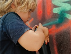 Caucasian three years old child painting graffiti on a wall at the street with a black t-shirt for the first time