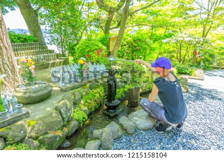 Caucasian tourist woman worshiping of Jizo Statue pouring water on Jizo's head with a ladle. Hase-dera Temple in Kamakura, Japan. Built to house a big wooden statue of Kannon goddess of mercy