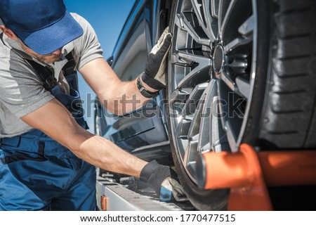Caucasian Towing Truck Worker in His 40s Preparing For Car Shipment. Checking Cargo Support Equipment. Transportation Theme.