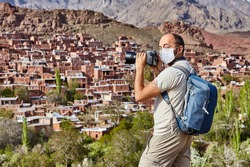 Caucasian traveler in a disposable protective surgical mask as a protection during coronavirus pandemic infection covid-19 is taking photos in Abyaneh, Iran, tourist season 2020.
