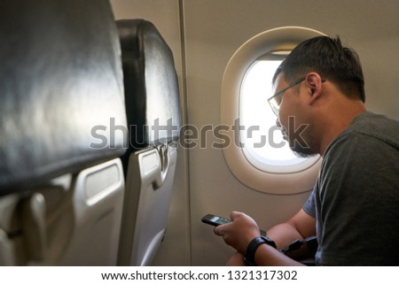 Caucasian traveller - the caucasian man who is sitting on the airplane seat and holding mobile phone, bag with watch is looking at his mobile phone #1321317302