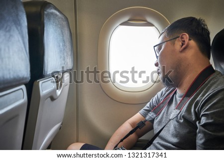 Caucasian traveller - the caucasian photographer man who is sitting on the airplane seat inside cabin and takes some rest before landing #1321317341