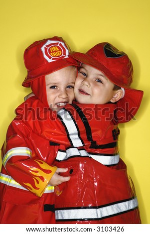 Caucasian twin boys dressed as firemen hugging against yellow background.