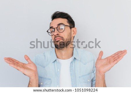 Caucasian unsure man make gestures doubtfully with hands with copy space. Uncertain young stylish stubble male with trendy round glasses wears demin blue shirt, shrugs shoulders being puzzled,confused #1051098224