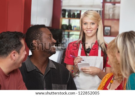 Caucasian waitress taking orders from diverse group of customers