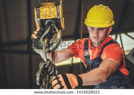 Caucasian Warehouse Lift Operator in His 30s. Heavy Duty Lifting Equipment.