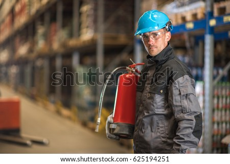 Caucasian warehouse worker with fire extinguisher Stockfoto ©