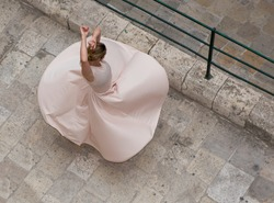 Caucasian white dancer, graceful woman stretching in the natural street background, ballet background, top view.The top view of the ballerina dancing in the street. Dancer in Valletta