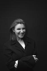 Caucasian white female model wearing male black suit in studio monochrome posing smile happy