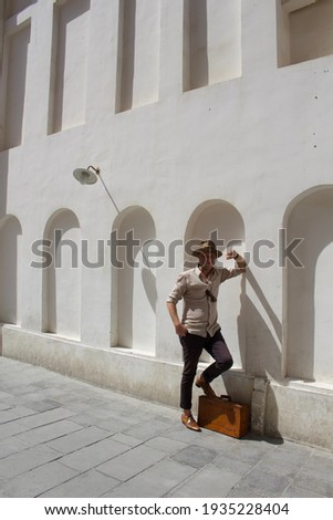 Caucasian, white, male in vintage travel outfit. Wearing light brown fedora, linen shirt and carrying vintage suitcase. Feeling of adventure travel and nostalgia. Arabic, Middle Eastern background. Stock photo ©