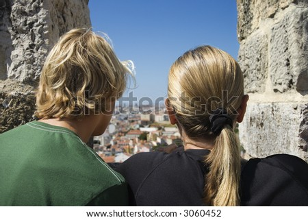 Caucasian woman and boy looking at view from castle structure in Lisbon, Portugal.