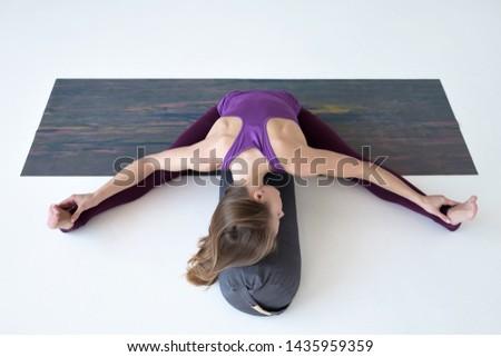Caucasian woman doing youga splits upavistha konasana on fitness mat. Full length studio shot
