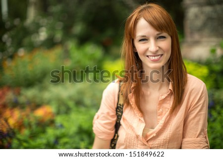 Caucasian woman female sitting in a park smiling face