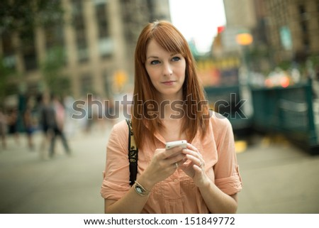 Caucasian woman female using iphone cellphone smartphone walking streets New York City