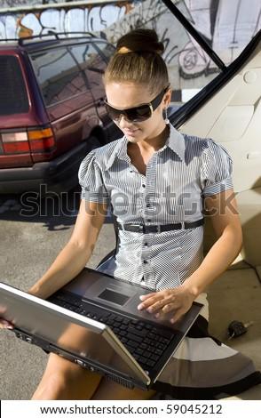 caucasian woman has a fan with laptop in black car