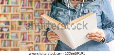 Caucasian woman holding a white book against some bookcases and shelves in a bookstore. Education concept and empty copy space for Editor's text. #1336659191