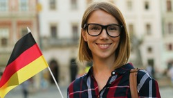 Caucasian woman in casual shirt with german flag posing on camera and smiling on the city street background.
