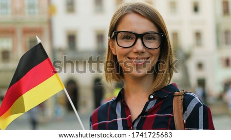 Caucasian woman in casual shirt with german flag posing on camera and smiling on the city street background. Stockfoto ©