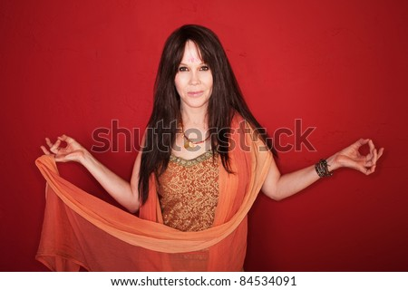 Caucasian woman in Indian attire with raised arms over red background
