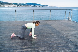 Caucasian woman in sportswear doing stamina exercises with effort endurance during morning training at boardwalk pier, strength female runner warming up before wellbeing jogging at seashore