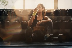 caucasian woman in sportswear sitting on floor near dumbells rack resting and rekaxing after having excercise and workout in gym and fitness club with sun flare, selective focused