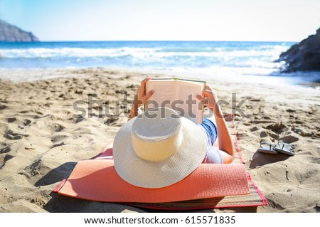 Caucasian woman is reading a book on a sandy beach wearing a straw hat