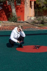 Caucasian Woman launches quadcopter and covers her eyes from the sunshine, squinting in the sun. Professional drone quadcopter with digital camera on Ground. New technology in the aero photo shooting