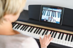 caucasian woman learning to play piano with video lessons. Concept of virtual learning. Selective focus on hand