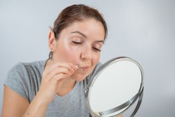 Caucasian woman looks in the mirror and removes the mustache herself with the help of tweezers. Hirsutism.