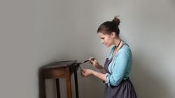 Caucasian woman paints with a brush restores furniture at home, the concept of creativity and conscious consumption, reuse