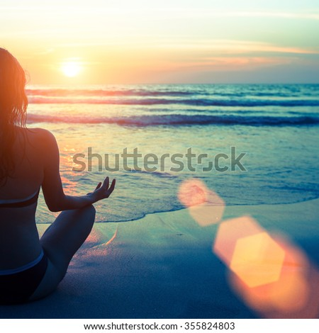 Caucasian woman practicing yoga at seashore during sunset. #355824803