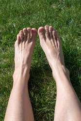 caucasian woman's lower leg and bare feet stretched out in green grass from perspective of sitting female