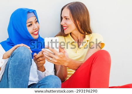 caucasian woman using phone together with asian muslim girl