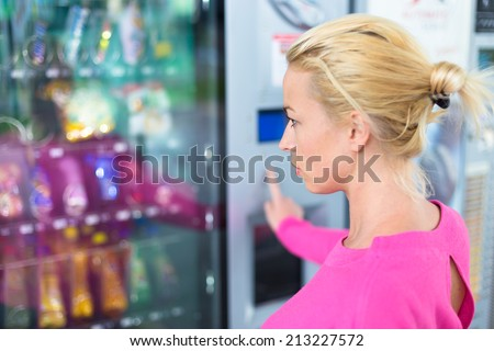 Caucasian woman wearing pink using a modern vending machine. Her right hand is placed on the key pad.